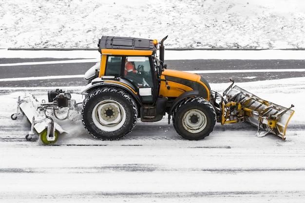 Duża maszyna do odśnieżania ciągnika w pracy na drodze podczas burzy śnieżnej w zimie.