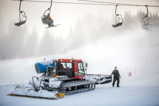 Duża maszyna do odśnieżania pracująca na stoku narciarskim pod krzesłami linowymi