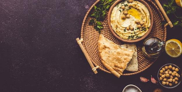 Duża miska domowego hummusu przyozdobionego ciecierzycą, czerwoną słodką papryką, natką pietruszki i oliwą z oliwek