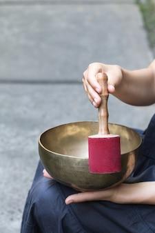 Duża miska tybetańskiego śpiewu w rękach kobiety