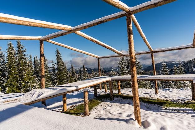 Duża, odsłonięta altana na szczycie góry stoi na ośnieżonej białej łące skąpanej w jasnym, zimnym słońcu karpat