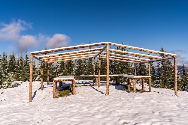 Duża, odsłonięta altana na szczycie góry stoi na ośnieżonej, białej łące skąpanej w świetle jasnego, zimnego słońca w karpatach