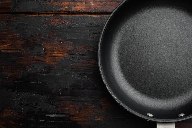 Duża patelnia z kopią miejsca na tekst lub jedzenie z kopią miejsca na tekst lub jedzenie, widok z góry płasko leżący, na starym ciemnym drewnianym stole tło