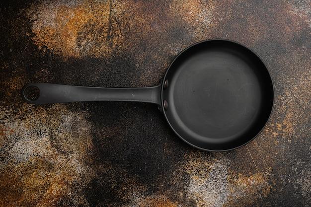 Duża patelnia z kopią miejsca na tekst lub jedzenie z kopią miejsca na tekst lub jedzenie, widok z góry płasko leżący, na starym ciemnym rustykalnym tle stołu