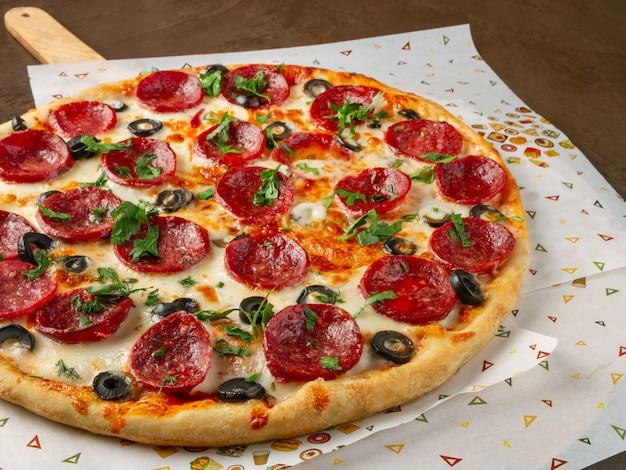 Duża pizza z salami i oliwkami posypana posiekanymi ziołami