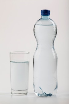 Duża plastikowa butelka wody i szkła