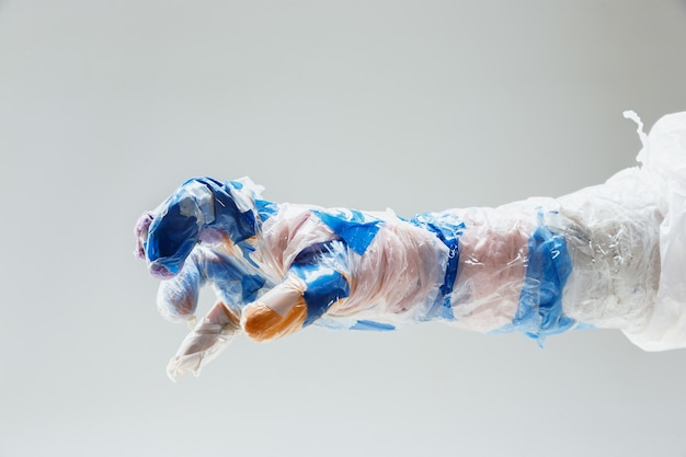 Duża plastikowa ręka wykonana ze śmieci na białym tle
