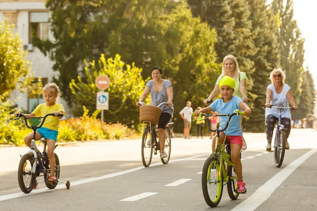 Duża rodzina 6 osób jeździ na rowerze w parku miejskim