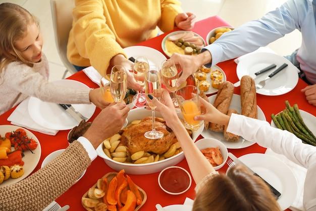 Duża rodzina brzęcząc kieliszkami podczas świątecznej kolacji w domu