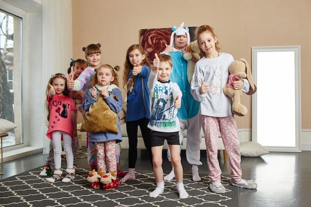 Duża rodzina, dzieci bawią się i bawią rano w domu. chłopcy i dziewczęta w nocnej piżamie, przyjazna duża rodzina.