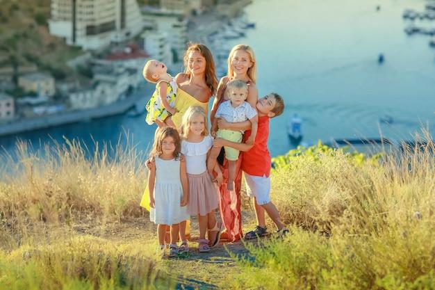 Duża rodzina krewnych razem dwóch matek i pięciorga dzieci stoi na szczycie góry nad wodą