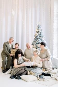 Duża rodzina na boże narodzenie wymieniająca prezenty siedząc na podłodze w domu