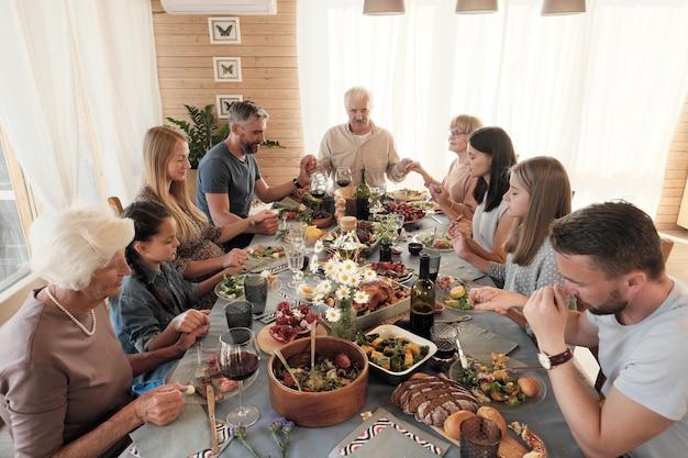 Duża rodzina siedząca przy stole trzymając się za ręce i zamykając oczy modli się przed posiłkiem