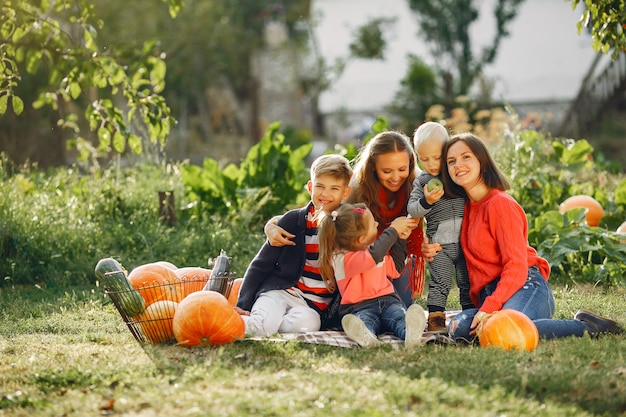 Duża rodzina siedzi na ogrodzie w pobliżu wielu dyń