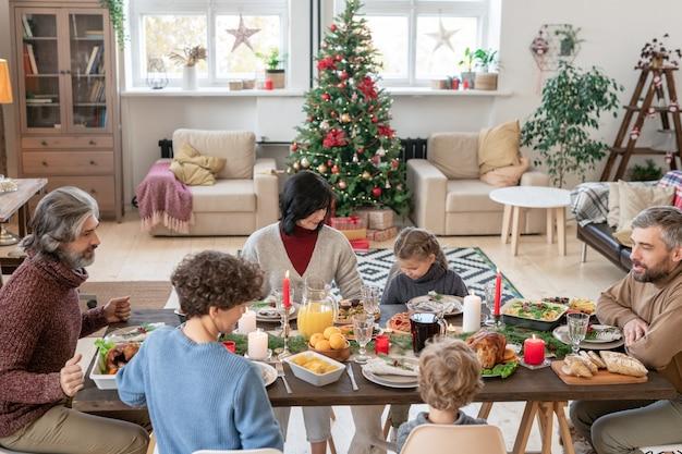 Duża rodzina składająca się z trzech pokoleń, siedząca przy zastawionym świątecznym stole, rozmawiająca i jedząca domowe jedzenie na świąteczny obiad w salonie