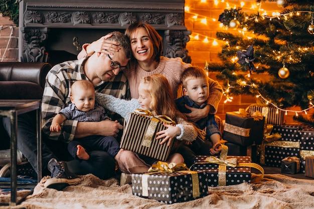 Duża rodzina w wigilię bożego narodzenia z prezentami przy choince