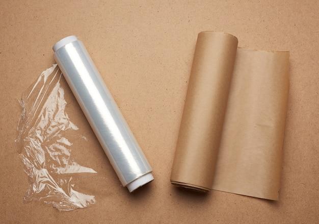 Duża rolka nawiniętej białej przezroczystej folii do pakowania żywności i rolka brązowego papieru rzemieślniczego