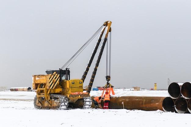 Duża rura na ładowaczu. ciągnik. roboty budowlane na morzu.