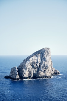 Duża skała na środku morza z niebieskim niebem