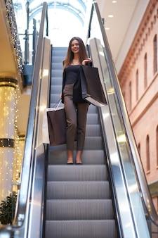 Duża sprzedaż. czarny piątek. uśmiechnięta pozytywna dziewczyna nosi modne ubrania z dużymi torbami na zakupy w sklepie.