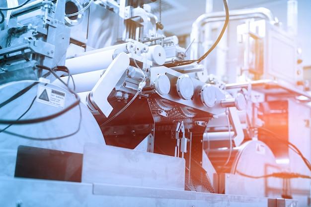 Duża stalowa maszyna z wałami i panelem sterowania