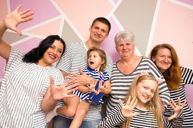 Duża szczęśliwa rodzina. matka z córką, synem i wnuczkami na jasnym tle