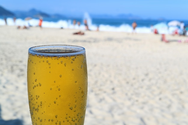 Duża szklanka zimnego piwa z niewyraźną plażą copacabana pełną ludzi, rio de janeiro, brazylia