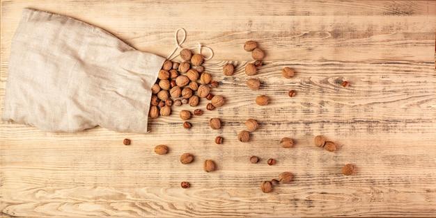 Duża torba z juty z orzechami i orzechami laskowymi. orzechy są rozrzucone na dużej drewnianej desce. drewniane tła. widok z góry.