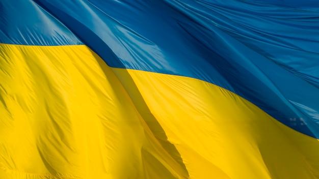 Duża ukraińska flaga, wykonana z wysokiej jakości materiału, trzepocze na wietrze, tworząc fale.