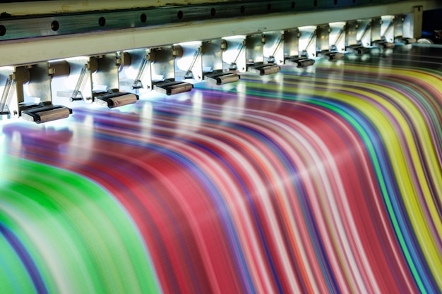 Duża wielokolorowa drukarka atramentowa pracująca na banerze winylowym