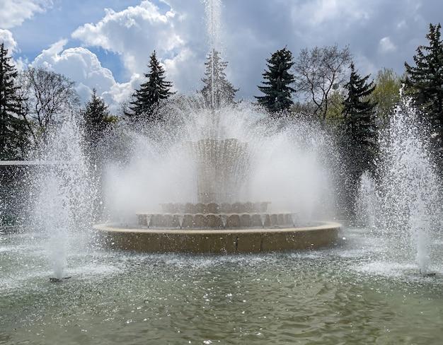 Duża wielopoziomowa fontanna z wieloma plamami w parku miejskim.