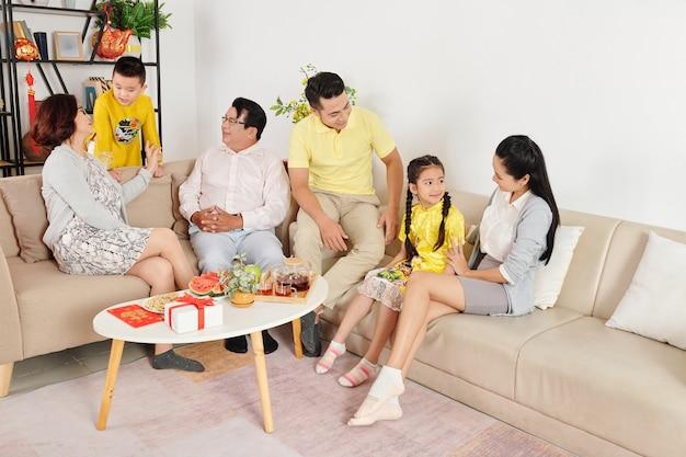 Duża wietnamska rodzina zebrała się w domu, aby porozmawiać i świętować tet, księżycowy nowy rok, kartki z najlepszymi życzeniami na stole