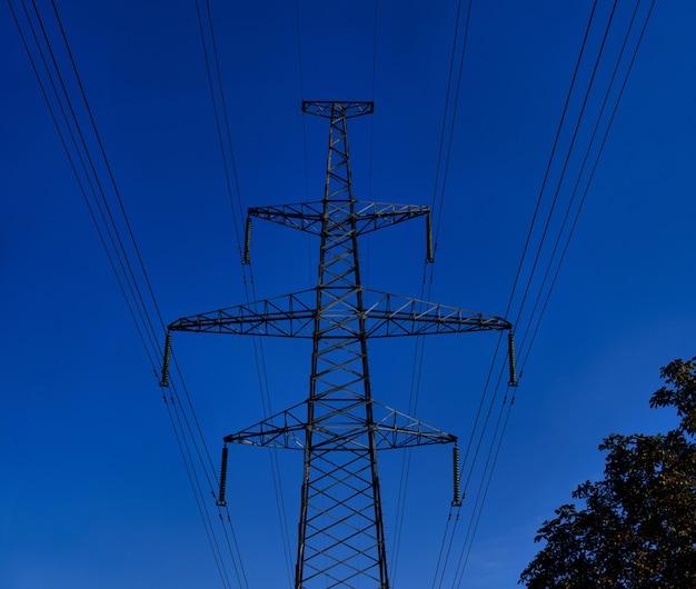 Duża wieża wysokiego napięcia z kablami zasilającymi. przemysłowy widok wysokiego napięcia