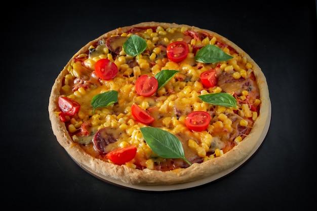 Duża włoska pizza z pomidorami i bazylią na czarnej przestrzeni.