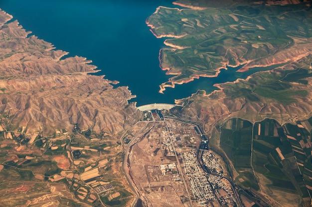 Duża zapora to betonowa zapora łukowo-grawitacyjna na rzece w kazachstanie. widok na tamę z okna samolotu