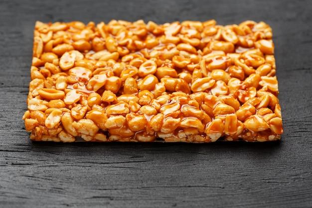 Duża złota płytka orzeszków ziemnych, baton w słodkiej melasie. kozinaki przydatne i smaczne słodycze wschodu