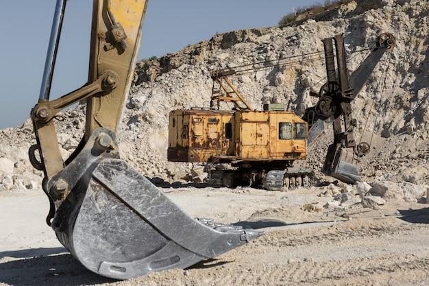 Duża żółta koparka gąsienicowa wydobywa skałę w kamieniołomie.