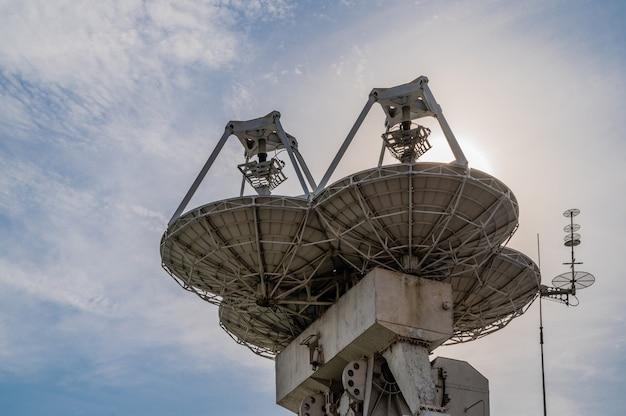 Duże anteny paraboliczne na tle błękitnego nieba z chmurami