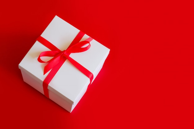 Duże białe pudełko z czerwoną wstążką na czerwonym widoku z góry, miejsce. koncepcja dużej sprzedaży