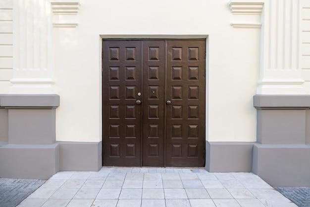 Duże brązowe drzwi przednie wykonane z drewna. wejście do budynku.