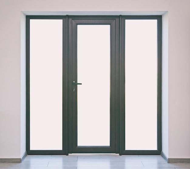 Duże brązowe drzwi wejściowe z białymi przestrzeniami zamiast szkła
