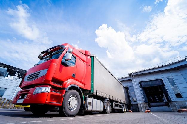 Duże ciężarówki w pobliżu magazynu na tle błękitnego nieba