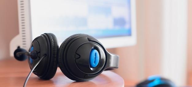 Duże czarne słuchawki leżą na drewnianym pulpicie projektanta dźwięku