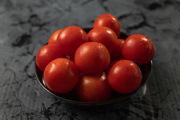 Duże czerwone pomidory na czarnym talerzu, na granitowym stole