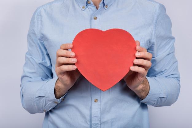 Duże czerwone pudełko w kształcie serca w męskich rękach. prezent dla ukochanej. prezent na walentynki