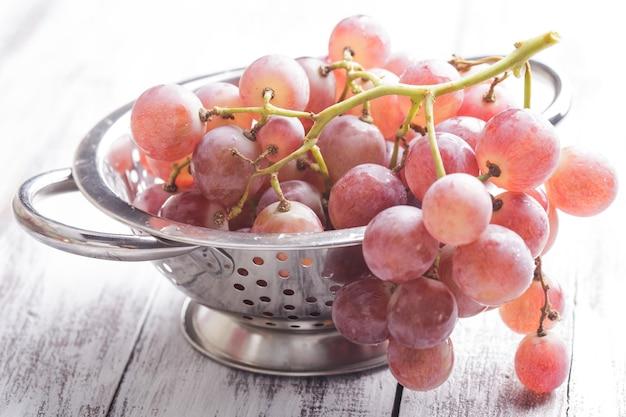 Duże czerwone winogrona w durszlaku na tle drewna