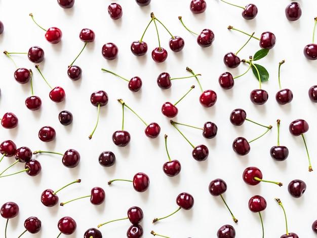 Duże dojrzałe czereśniowe jagody z liśćmi i kroplami wodny tło. naturalne lato jedzenie tła.