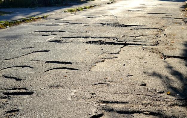 Duże doły na drodze z jezdni asfaltowej