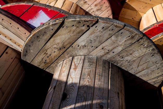 Duże drewniane szpule kablowe, przechowywane w fabryce kabli elektrycznych.