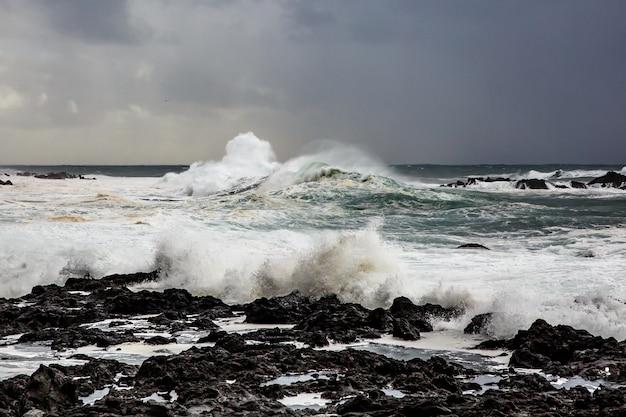 Duże fale rozbijające się w pobliżu skalistego brzegu. burza oceaniczna